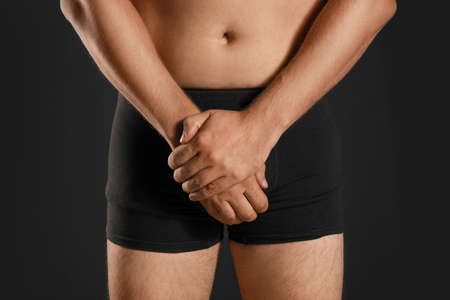 Man suffering from pain on black background, closeup. Urology problems