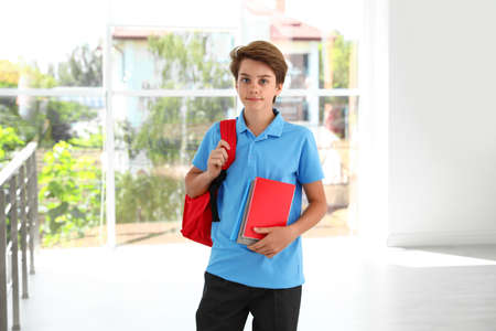 Happy boy in school uniform with backpack indoors