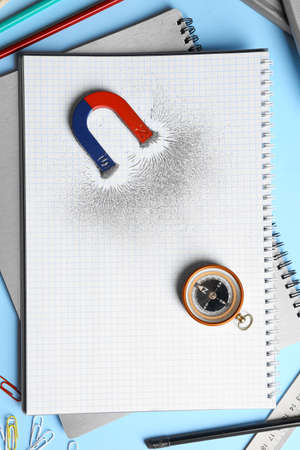 Notebook, stationery, compass and magnet with iron powder on blue background, flat lay