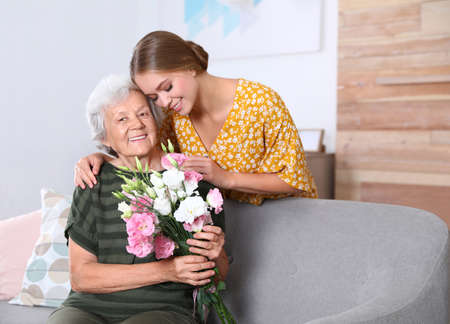 Young woman congratulating her senior mom at home. Happy Mother's Day Standard-Bild