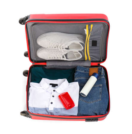 Packed suitcase with deodorants and clothes on white background Stock Photo