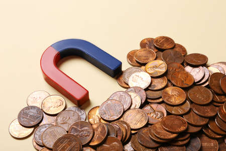 Magnet attracting coins on beige background, closeup