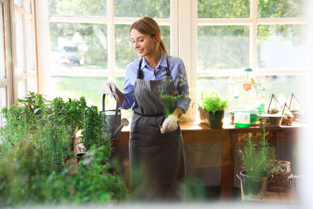 Young woman with watering can taking care of home plants in shop, view through window