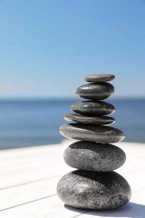 Stack of stones on wooden pier near sea, space for text. Zen concept