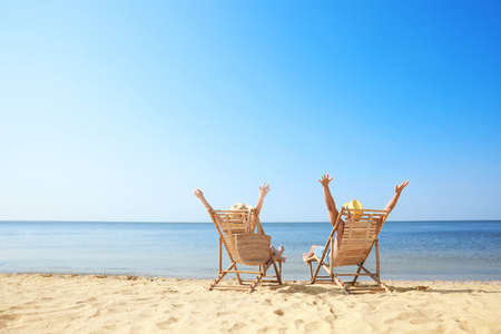 Young couple relaxing in deck chairs on beach Stok Fotoğraf