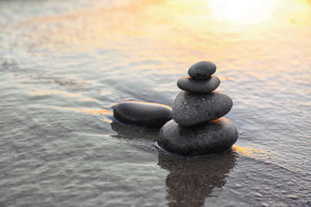 Dark stones on sand near sea at sunset, space for text. Zen concept