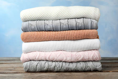 Stack of warm clothes on wooden table against light blue background. Autumn season