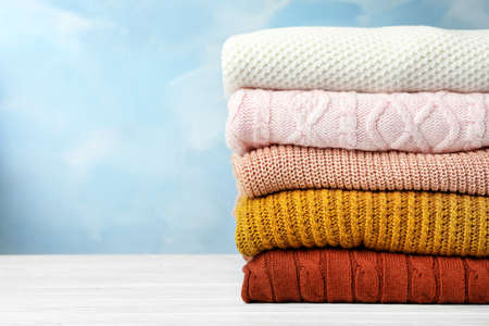 Stack of warm clothes on white wooden table against light blue background, space for text. Autumn season