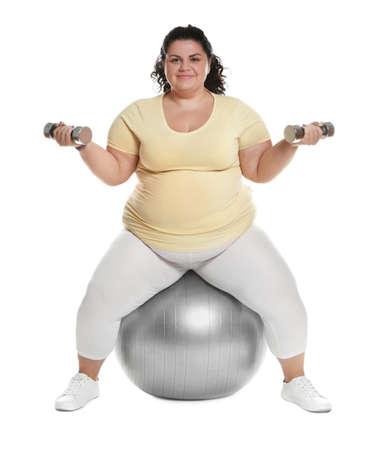 Femme en surpoids faisant de l'exercice sur fit ball avec haltères contre fond blanc