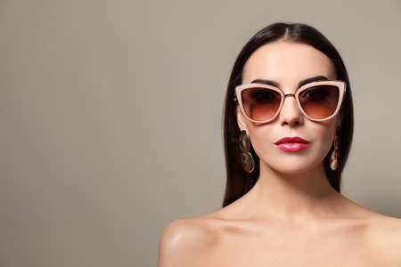 Beautiful woman in stylish sunglasses on beige background. Space for text