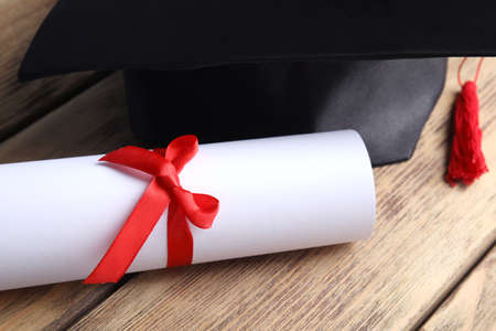 Graduation hat and student's diploma on wooden table, closeup 写真素材