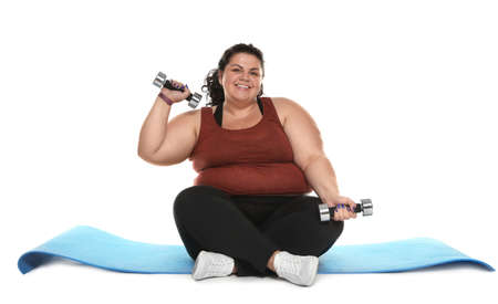 Overweight woman with mat and dumbbells on white background