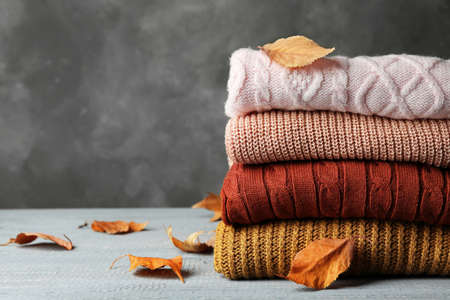 Stack of warm clothes and autumn leaves on wooden table against grey background. Space for text Archivio Fotografico