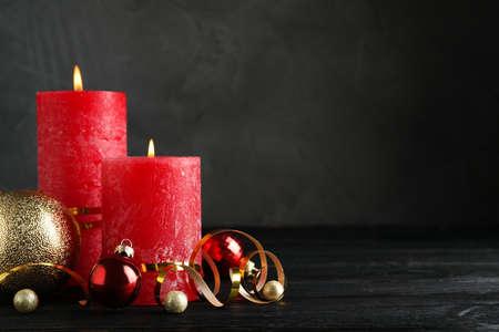 Schöne Weihnachtskomposition mit brennenden roten Kerzen auf schwarzem Holztisch. Platz für Text
