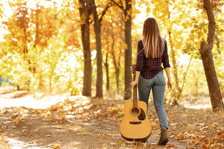 Teen girl with acoustic guitar in autumn park, back view