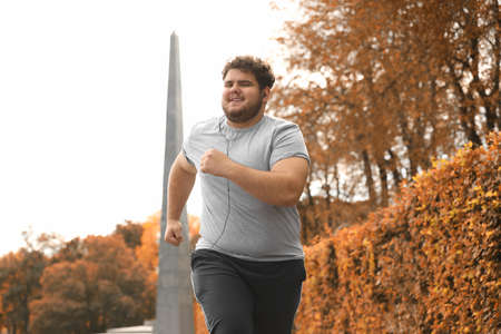 Young overweight man running in park. Fitness lifestyle Archivio Fotografico - 132239797