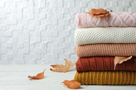 Stack of warm clothes and autumn leaves on white wooden table against textured wall. Space for text Zdjęcie Seryjne