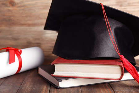 Graduation hat, books and student's diploma on wooden table, closeup