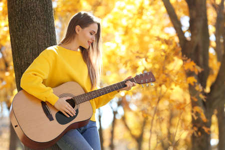 Teen girl playing guitar in autumn park 写真素材