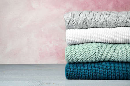 Stack of warm clothes on grey wooden table against light background, space for text. Autumn season