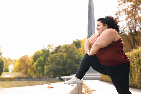 Beautiful overweight woman doing sport exercises in park