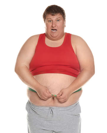 Emotional overweight man measuring waist with tape on white background Imagens