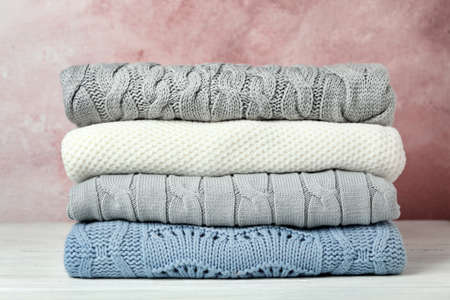 Stack of warm clothes on white wooden table against light background. Autumn season Zdjęcie Seryjne