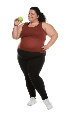 Happy overweight woman with apple on white background