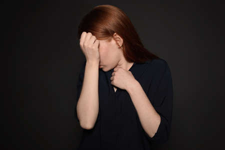 Upset young woman crying against dark background Stock Photo