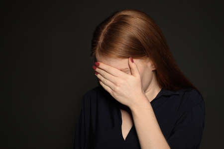 Upset young woman crying against dark background. Space for text