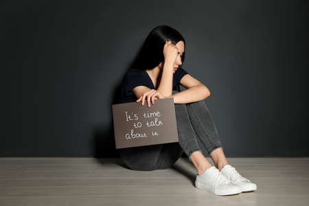 Young woman holding card with words ITS TIME TO TALK ABOUT IT while sitting near grey wall Stock Photo