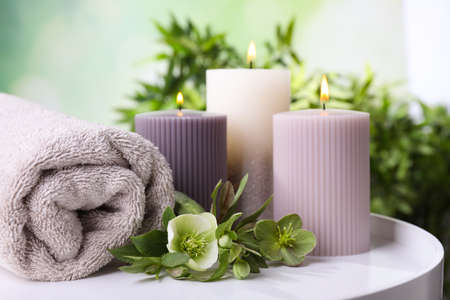 Burning candles, towel and flowers on white table against blurred green background, space for text Stock fotó