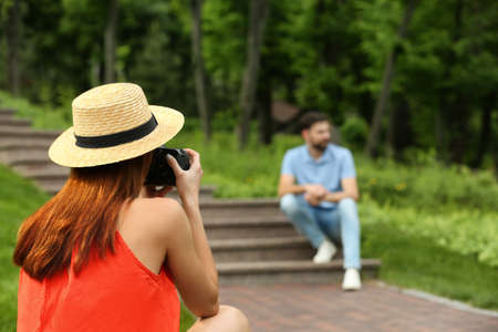 Photographer taking photo of man with professional camera in park