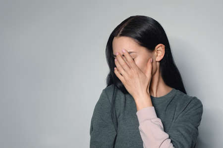 Upset young woman crying against light background. Space for text