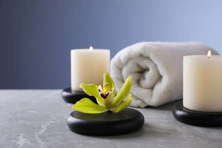 Spa stones with exotic flower and burning candles on grey table, space for text