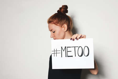 Young woman holding #METOO card against light background