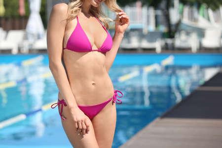 Sexy young woman in stylish bikini near swimming pool on sunny day