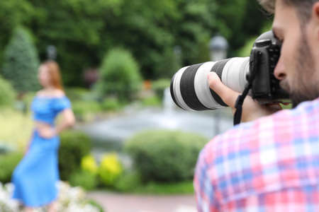 Photographer taking photo of woman with professional camera in park