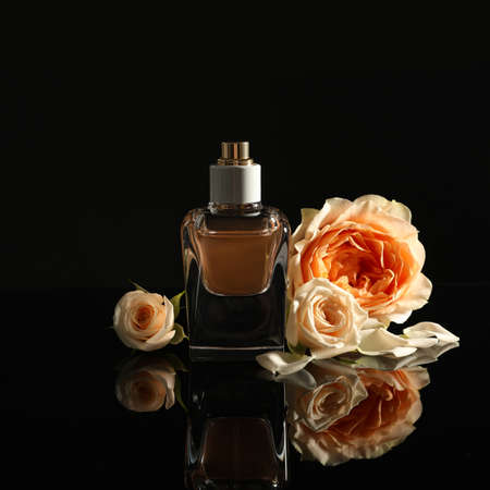 Elegant bottle of perfume and beautiful flowers on black background