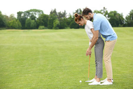 Coach teaching woman to play golf on green course