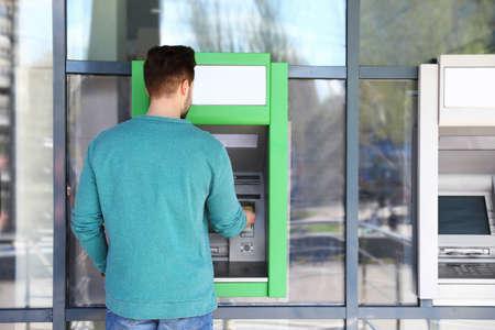 Young man using modern cash machine outdoors