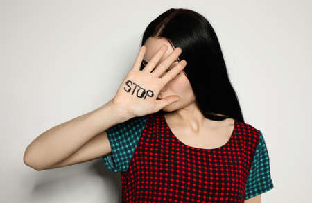 Young woman with word STOP written on her palm against light background