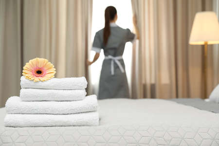 Stack of clean towels with flower on bed and blurred chambermaid in hotel room, closeup. Space for text Stok Fotoğraf