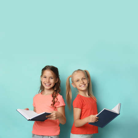 Portrait of little girls reading books on turquoise background