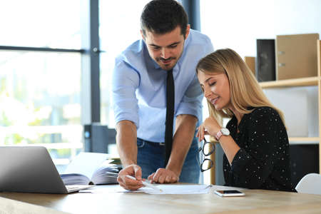 Male business trainer coaching young woman in office Archivio Fotografico