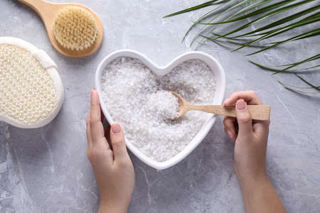 Woman holding heart shaped plate with sea salt for spa scrubbing procedure at grey marble table, top view Stock Photo