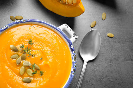 Delicious pumpkin soup in bowl on grey table, flat lay