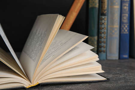 Open hardcover book on grey stone table, closeup Stock Photo