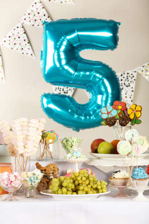 Blue number five balloon over table with delicious treats at Birthday party indoors