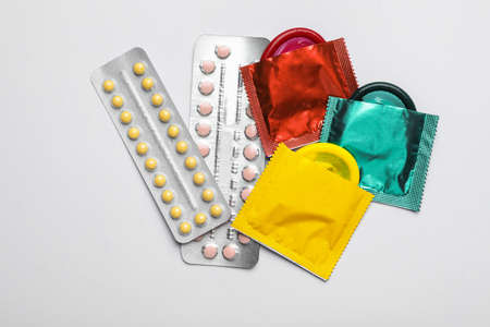 Condoms and birth control pills on white background, top view. Safe sex concept